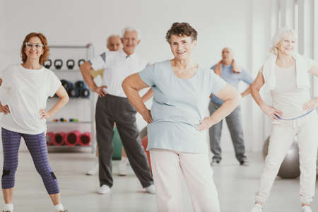 Happy senior woman holding hips during gymnastic classes for elderly people