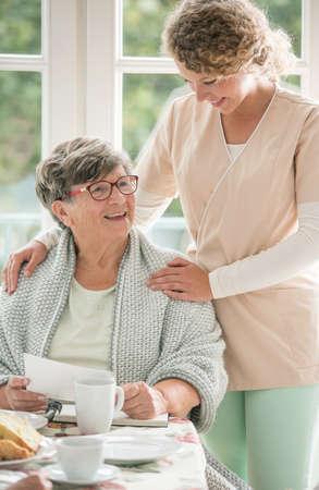 Señora mayor positiva emplazamiento en la mesa y sonriendo a su joven enfermera