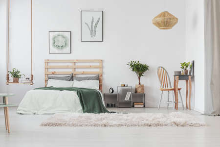 Scandinavian bedroom interior with elegant dresser and warm carpet, minimal posters in black frames on white wall of classy