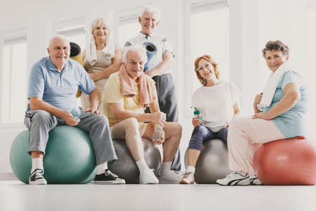 Low angle on smiling active elderly people on balls after physical classes in sport club Banco de Imagens