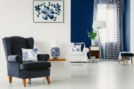 Floral accents in bright living room interior in blue and white colors, real photo