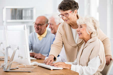 Smiling elderly lady helping her friend during computer classes for seniors at third age university