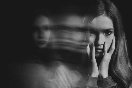Immagine in bianco e nero di una giovane e bella donna rossa spaventata con disturbo da stress post traumatico che ha problemi di sonno Archivio Fotografico