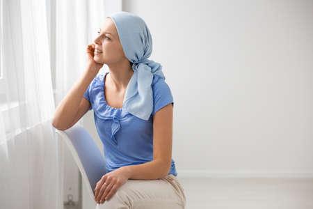 Adolescente sonriente que sufre de un tumor cerebral, con un pañuelo azul en la cabeza y sentada en una silla en la sala de espera del hospital, mirando por la ventana, copia el espacio en la pared vacía