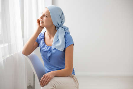 Smiling teenage girl suffering from brain tumor, wearing blue headscarf and sitting on chair in hospital waiting hall, looking through the window, copy space on the empty wall Zdjęcie Seryjne