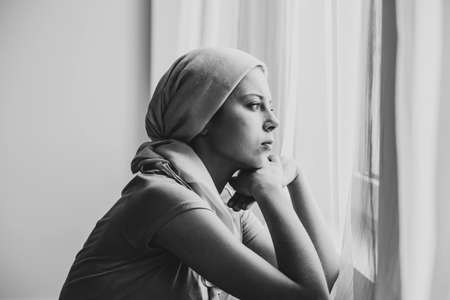 Black and white photo of thoughtful young girl suffering from ovarian cancer wearing headscarf and looking through the window in medical center Stock Photo