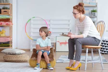 Boy with Asperger syndrome sitting on pouf during therapy with psychiatrist Stock Photo