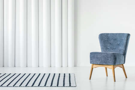 Trendy blue armchair in empty white interior with striped rug Imagens
