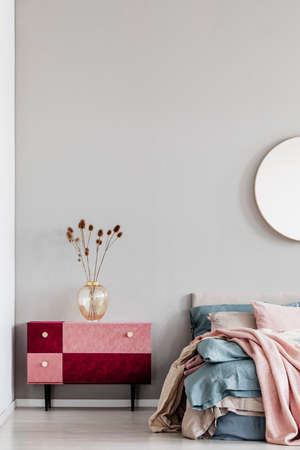 Flowers in elegant glass vase on diy velvet covered pastel pink and burgundy nightstand next to cozy bed with blue and beige bedding