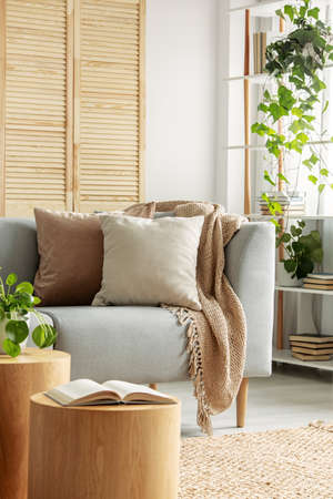 Urban jungle in natural living room with beige pillows on grey couch and open book on wooden table