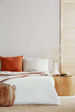 Copy space on white empty wall of natural bright bedroom with wooden accents and king size bed Stock Photo