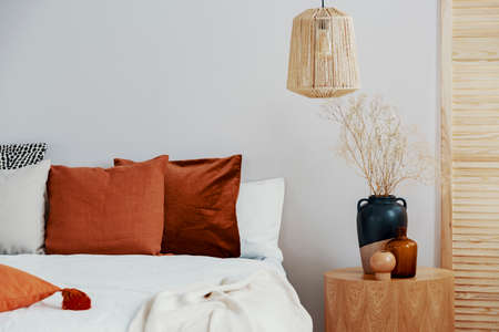 Brown pillows on white bed in natural bedroom interior with wicker lamp and wooden bedside table with vase Stock Photo