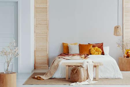 Oreillers marron et orange sur lit blanc à l'intérieur de la chambre naturelle avec lampe en osier et table de chevet en bois avec vase