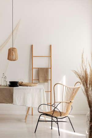 Stijlvolle rieten stoelen naast tafel bedekt met wit tafelkleed, echte foto met kopieerruimte op lege muur