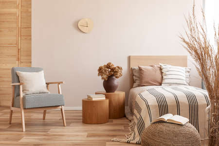 Stylish retro armchair with white pillow next to two round wooden tables with books and vase with flowers in beige bedroom interior