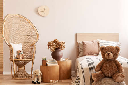 Teddy bear sitting on pouf in natural beige kids room with stylish furniture