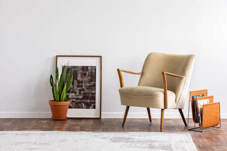 Abstract graphic in wooden frame next to green plant in ceramic pot and elegant beige armchair and orange magazine rack, real photo