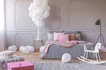 Real photo of a romantic bedroom interior with birthday decorations like balloons, cake and present Stock Photo