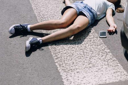Fille inconsciente allongée dans une rue à côté de son téléphone portable