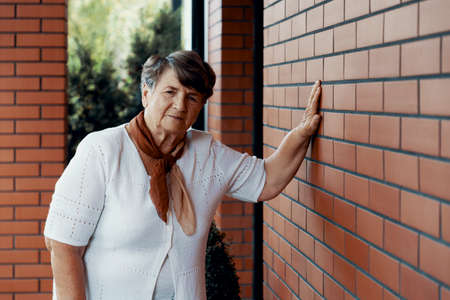 Elderly lady leaning against a brick wall of her home
