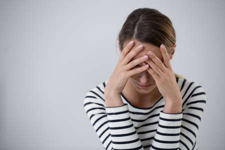 Schöne junge Frau, die an Stimmungsstörungen leidet und ihren Kopf hält, Foto mit Kopienraum