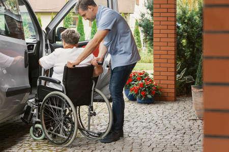 Auxiliar enfermero con señora mayor en silla de ruedas ayudándola a subir al coche Foto de archivo