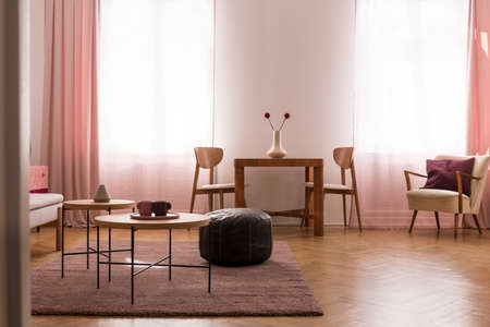 Wooden table and pouf on carpet in living room interior with chairs, armchair and windows. Real photo