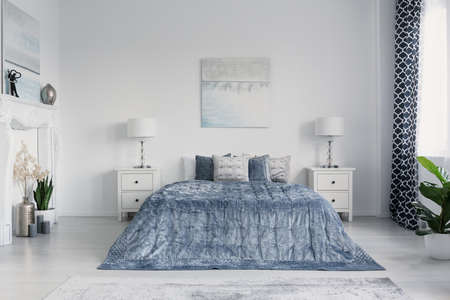 Velvet blue duvet on king size bed in elegant new york bedroom with white furniture
