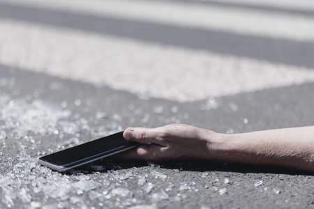 Close-up of a hand holding a mobile phone. Pieces of glass on the street