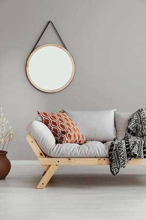 Round mirror in wooden frame on the wall of bright beige living room with comfortable sofa with patterned pillow and striped blanket, real photo Reklamní fotografie - 114497057