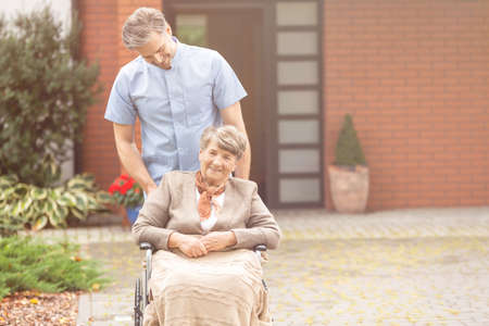 Smiling handsome male nurse and senior pensioner on wheelchair in the garden of nursing home 스톡 콘텐츠