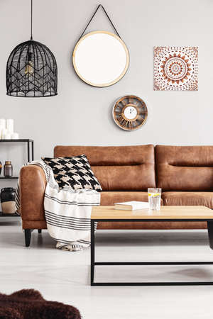 Round mirror, wooden clock and ethno graphic on the beige wall of elegant living room interior with leather couch with patterned pillow and stylish black chandelier, real photo Stock Photo