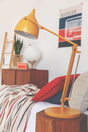 Closeup of orange lamp on bedside table in vintage bedroom, real photo