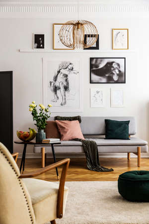 Posters above grey sofa with pillows in living room interior with flowers and armchair. Real photo