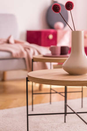 Red flowers in white vase on round wooden table in living room interior with carpet. Real photo