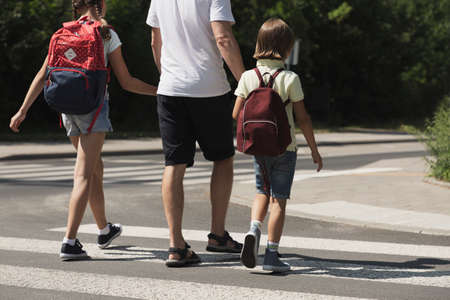 Father crossing a street with his kids while coming back from school Reklamní fotografie - 114497163
