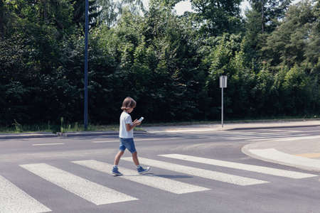 Boy crossing the street while looking at his smartphone Banco de Imagens
