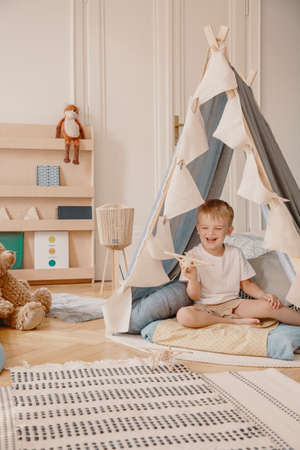 Cute little boy sitting in tent in stylish kids playroom in modern apartment, real photo