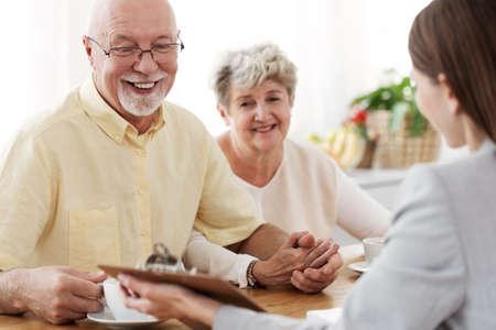 Uśmiechnięta para małżeńska rozmawiająca z agentem nieruchomości