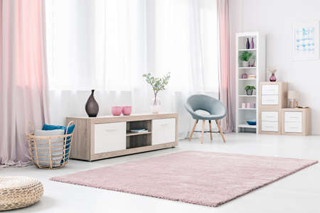 Bright living room interior with wooden cabinet, grey stylish chair and fluffy pastel pink rug