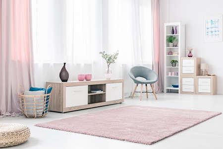 Interior luminoso salón con mueble de madera, elegante silla gris y mullida alfombra rosa pastel