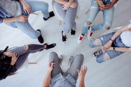 Bovenaanzicht van lastige tieners en hun therapeut tijdens professioneel gesprek met counselor Stockfoto