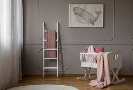 Pink blanket on white cradle in grey baby's bedroom interior with poster and ladder. Real photo
