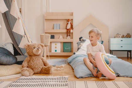 Cute child sitting on a bed in scandinavian kids play room with toys, tent and wooden furniture Stock Photo