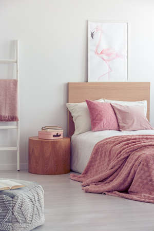 Pink pillows and blanket on white bedding in fashionable girls bedroom interior Stock Photo