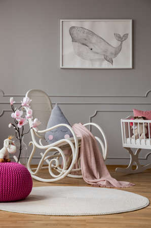 Pink pouf and flowers in grey babys bedroom interior with poster and rocking chair. Real photo Stock Photo