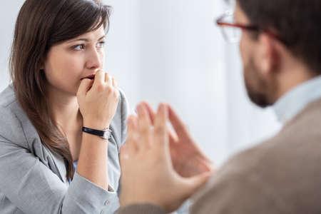 Triest mooie jonge vrouw met sociale problemen tijdens psychotherapie