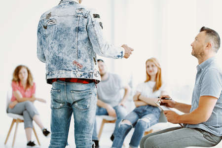 Young teenager during group therapy session with professional therapist Stock Photo