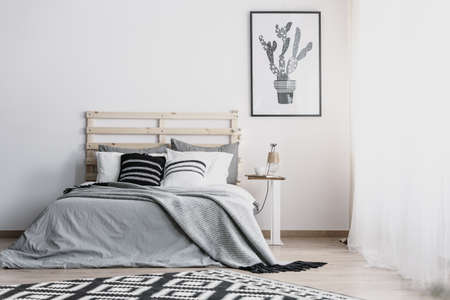 Black and white cactus in pot graphic on the empty white wall of bright bedroom with cozy king size bed , real photo with copy space Archivio Fotografico