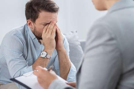 Apuesto joven empresario triste con problemas durante la sesión con el consejero